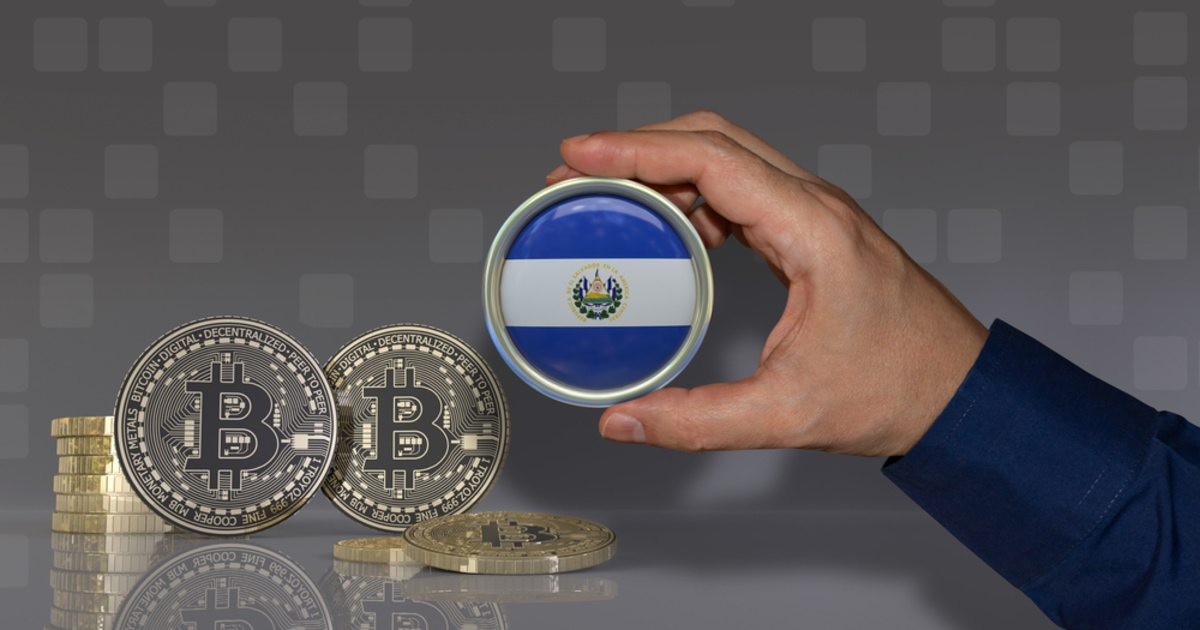 A hand holding aEl Salvador's flag coin and bitcoin on the desk