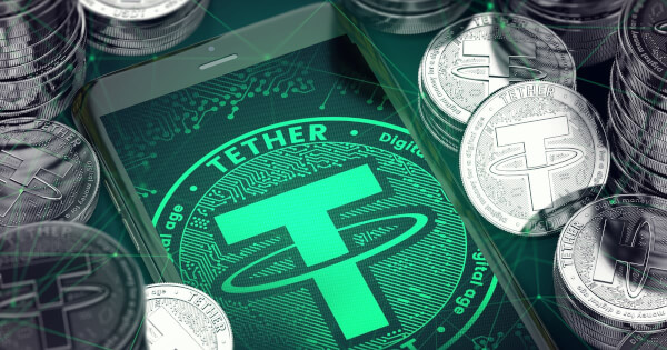 Smartphone with green Tether symbol on-screen among Tether coins.