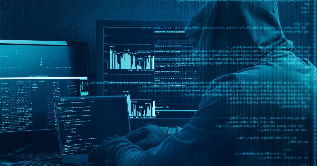 Hacker working on a code on dark digital background with digital interface around.